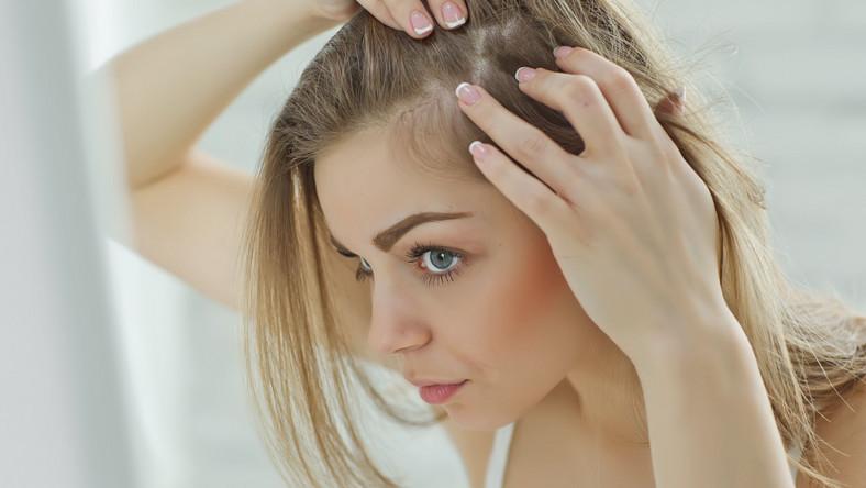Kobieta oglada skórę głowy, włosy
