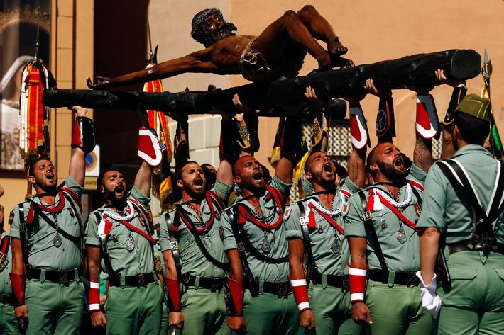 Spanish legionnaires sing an anthem as they carry a statue of the Christ of Mena during a ceremony b