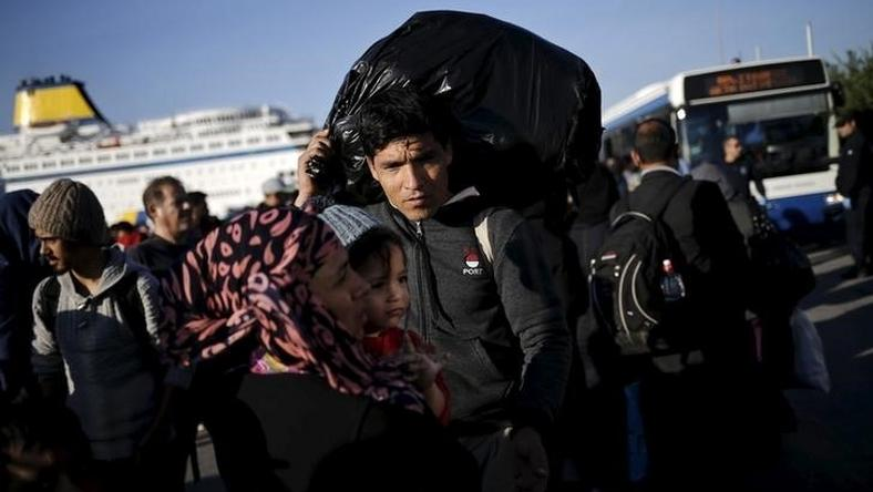 An Afghan refugee carries his belongings as he and his family wait to board a bus, following the arrival of refugees and migrants by the Blue Star Patmos passenger ferry from the island of Lesbos at the port of Piraeus, near Athens, Greece, October 14, 2015. REUTERS/Alkis Konstantinidis