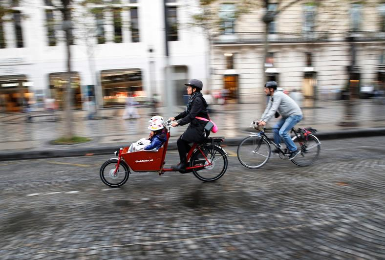 "Parisians ride their bicycles on the Champs Elysees during a ""day without cars."""