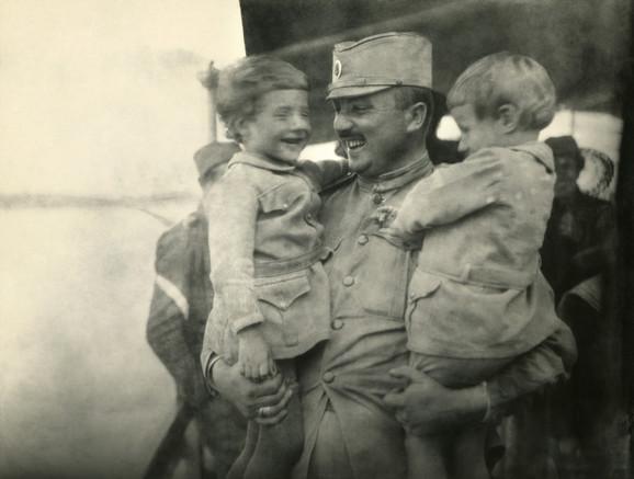 Srpski vojnik u zagrljaju svoje dece na savskom pristaništu u Beogradu, 1918.
