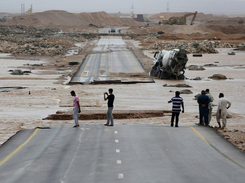 People visit a road which has been cut by the flood water after Cyclone Merkunu in Salalah, Oman, on May 26, 2018. Cyclone Merkunu blew into the Arabian Peninsula on Saturday, drenching arid Oman and Yemen with rain, cutting off power lines.