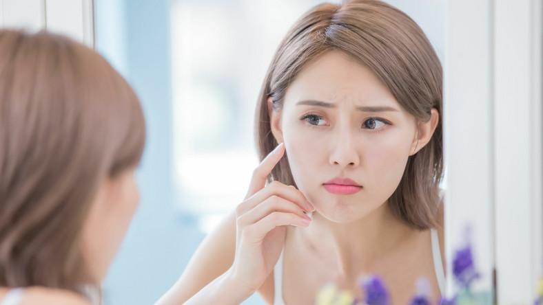 Kobieta ogląda się w lustrze