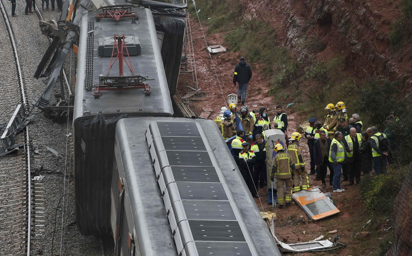Firefighters, police and other officials survey the scene after a commuter train derailed between Te