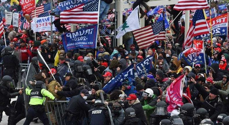 Trump supporters clash with police and security forces as they push barricades to storm the US Capitol in Washington D.C on January 6, 2021.