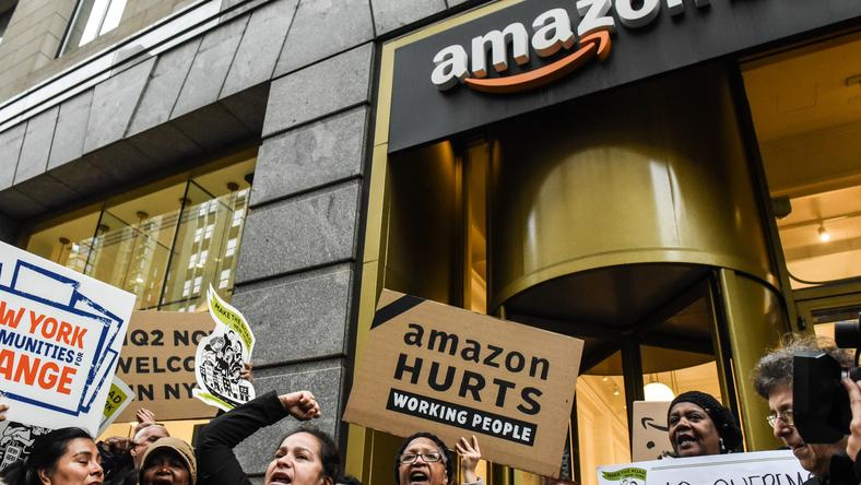Protestors hold up anti-Amazon HQ2 signs outside an Amazon store in Manhattan.