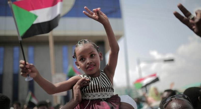 A young Sudanese girl waves country's flag