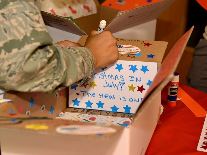 An Air Force Staff Sgt. prepares a care package box for a deployed colleague at Royal Air Force base Mildenhall, England in July 2018.
