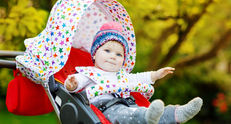 Cute little beautiful baby girl of 6 months sitting in the stylish pram or stroller and waiting for mom