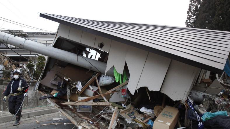 Strażak ochotnik obok domu przebitego przez słup wysokiego napięcia w Rikuzentakada w prefekturze Iwate