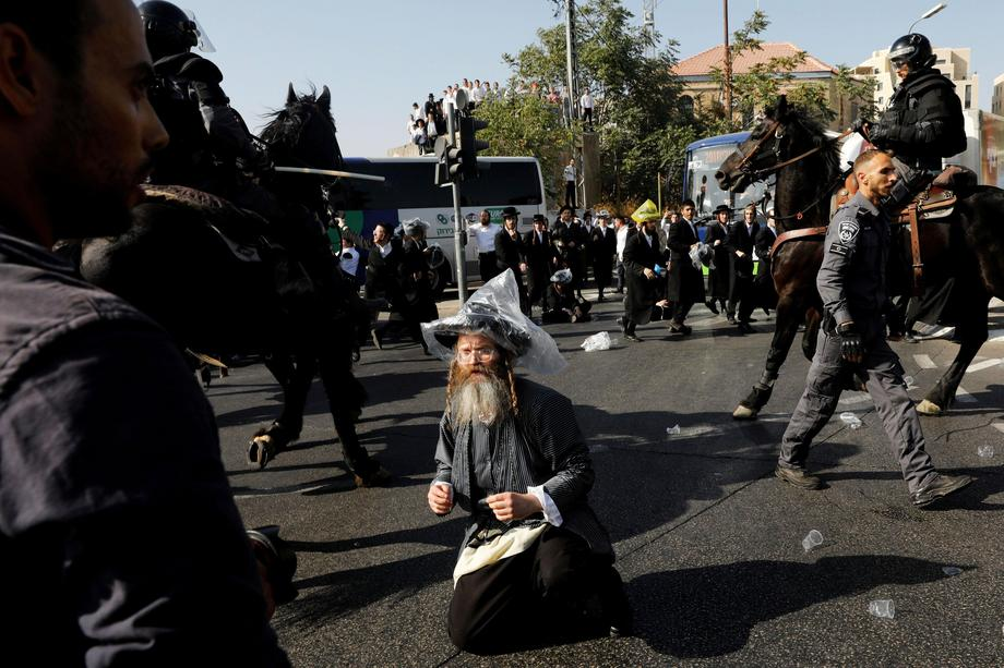 Israeli ultra-Orthodox Jewish men clash with police at a protest against the detention of a member o