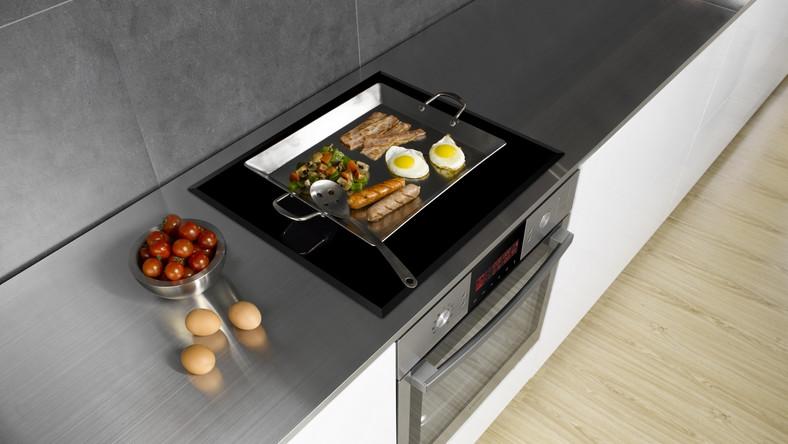 Na polu AnyDish możemy gotować w naczyniach o dowolnym kształcie i rozmiarze. To otwarta powierzchnia grzejna pozwalająca na umieszczenie na niej różnej wielkości naczyń. Urządzenie podgrzeje tylko tą powierzchnię, na której stoi naczynie.