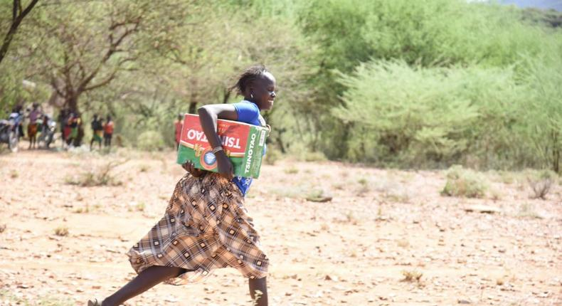 Resident of Tiaty Subcounty with the carton of beer donated (Nation)