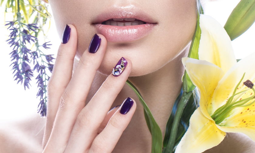 Beautiful girl with flowers, and design nails manicure. beauty face. Close up