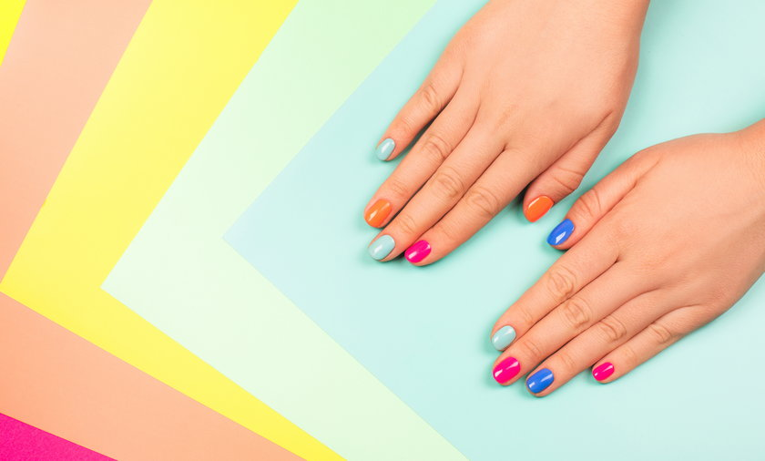 Neon manicure on multicolored bright background in trendy colors.