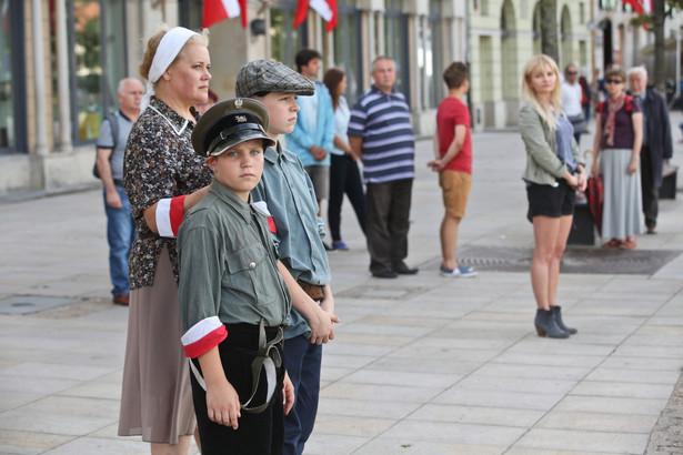 """Godzina """"W"""" na Krakowskim Przedmieściu w Warszawie. Zatrzymali się przechodnie, stanęły pojazdy, przez minutę wyły syreny alarmowe, rozległy się kościelne dzwony."""