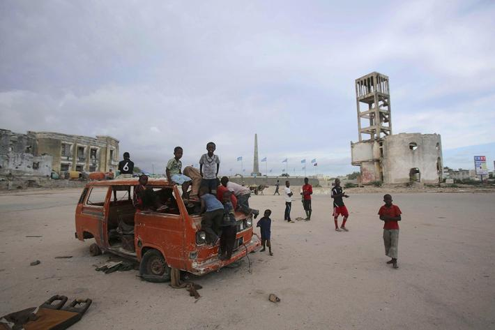 Children play on an abandoned truck in front of the destroyed former parliament building in Mogadish