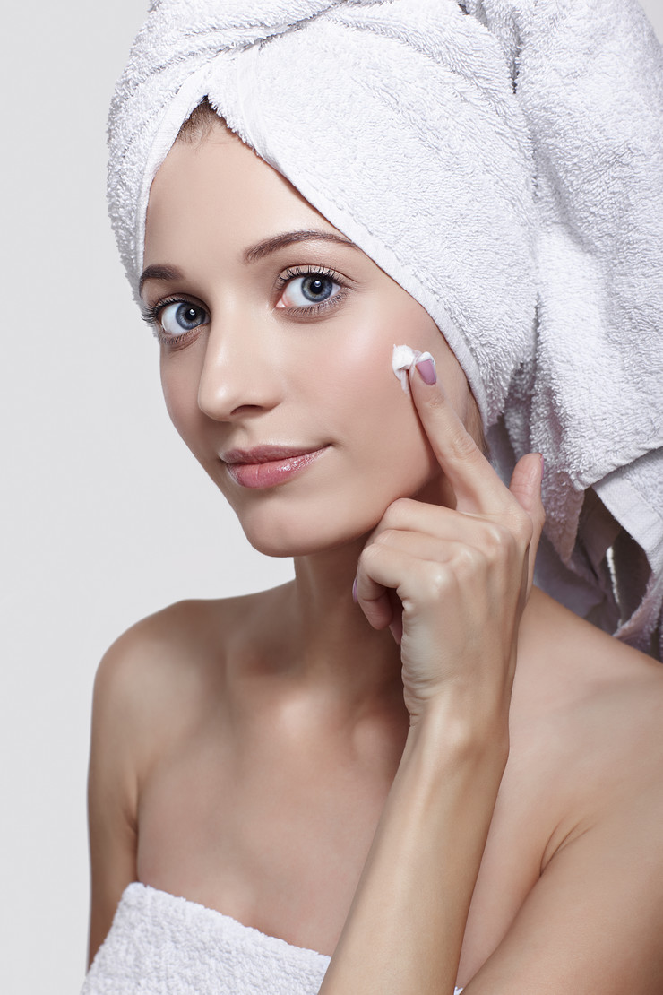 stock-photo-portrait-of-beautiful-girl-rubbing-cream-on-her-cheek-young-woman-with-bath-towel-on-the-head-1194250060