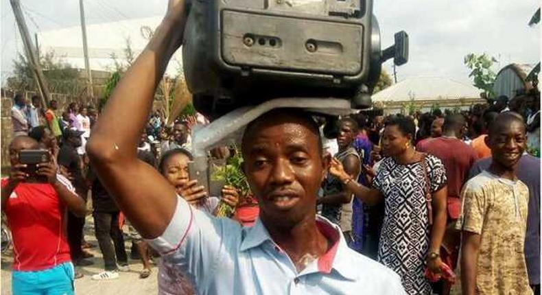 A man makes his protest by holding a generator set on his head.