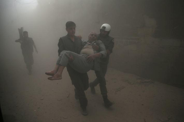 Civil defense members carry an injured man after an air strike in the rebel-held Douma neighbourhood