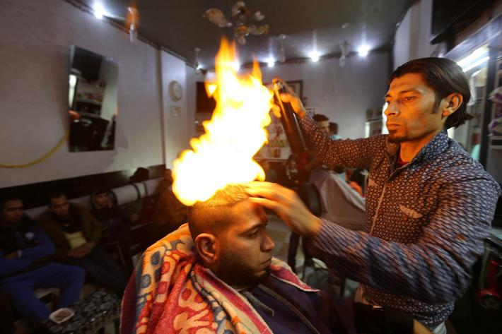 Palestinian barber Ramadan Odwan styles and straightens the hair of a customer with fire at his salo