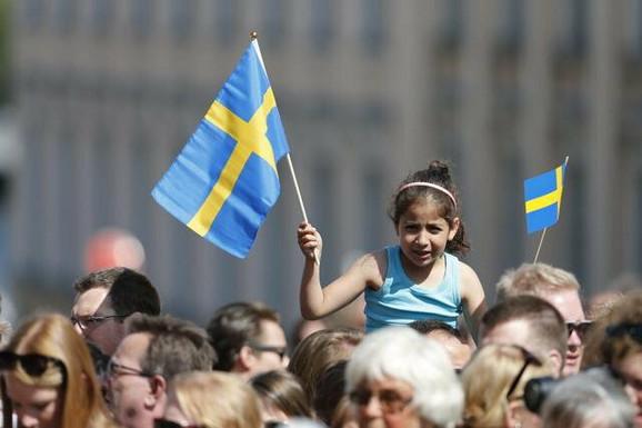 Devojčica maše švedskom zastavom
