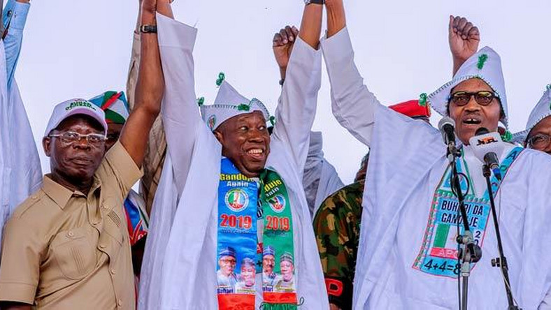 Buhari and APC Chairman Oshiomhole hold aloft Ganduje's hand in Kano at a campaign rally (Presidency)