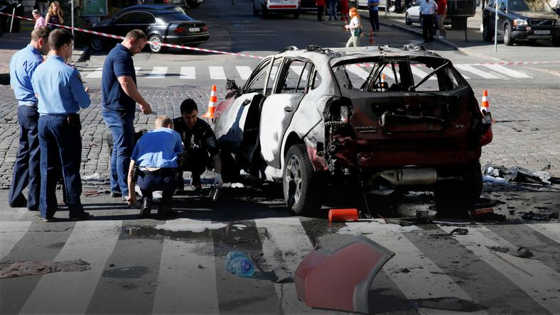 Investigators inspect a damaged car at the site where journalist Pavel Sheremet was killed by a car bomb in central Kiev