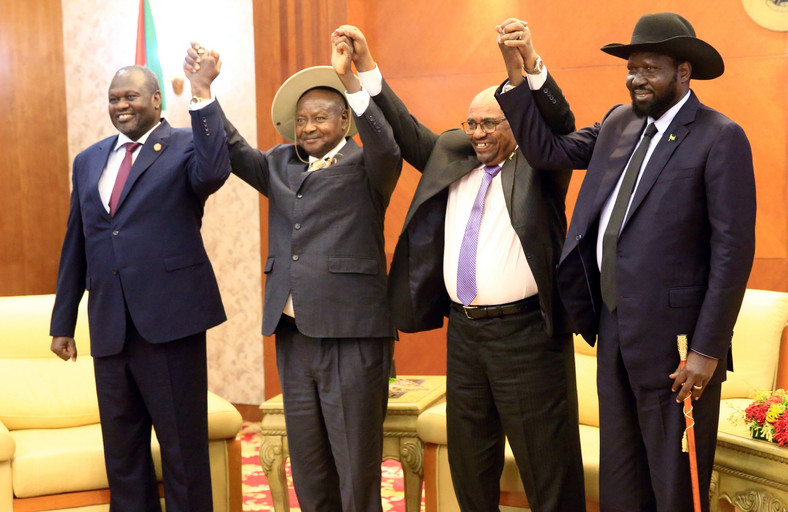 Sudan's President Omar Al-Bashir hold hands with Uganda's President Yoweri Museveni, South Sudan's President Salva Kiir and South Sudan rebel leader Riek Machar during a South Sudan peace meeting in Khartoum.