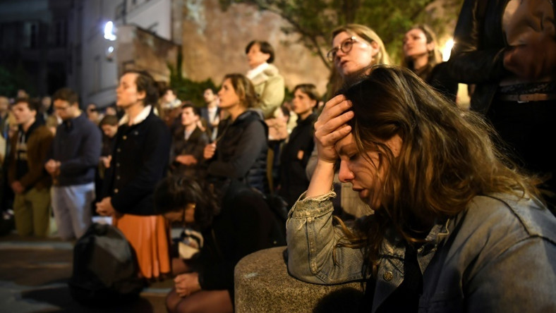 Onlookers react as they watch flames engulf Notre-Dame Cathedral in Paris on April 15, 2019