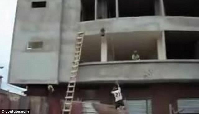 ...a potom skače uz pomoć konopca za koji je zavezana kofa sa cementom