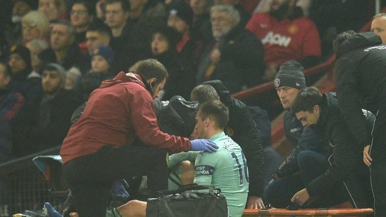 Arsenal defender Rob Holding receives medical attention at Old Trafford