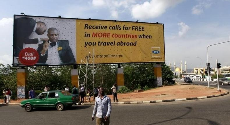A man walks in front of an advertisement billboard of MTN phone company in Abuja, Nigeria May 25, 2015.