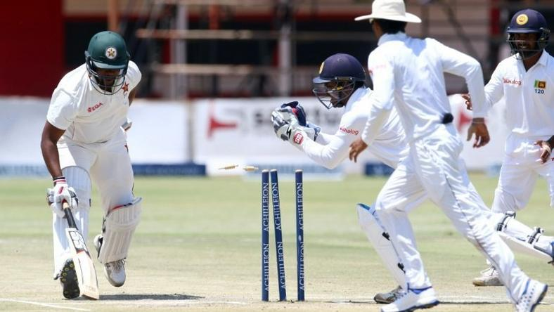 Zimbabwe's batsman Hamilton Masakadza (left) survives a run out attempt by wicketkeeper Kusal Janith Perera during a Test match in Harare, on November 2, 2016