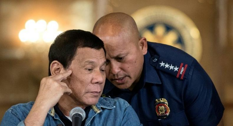 Philippine President Rodrigo Duterte (L) talks to Philippine National Police (PNP) Director General Ronald Dela Rosa (R) during a press conference in Manila on January 30, 2017