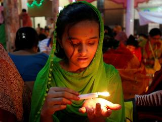 A girl pours melted hot wax on her hand from a candle as she sits on the floor of a temple to observe Rakher Upabash for the last day, in Dhaka, Bangladesh