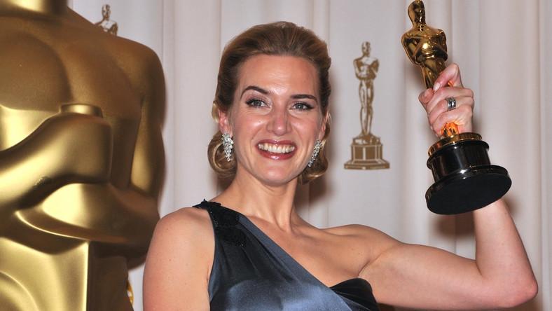 """W 2005 roku znana między innymi z """"Titanica"""" Kate Winslet wystąpiła gościnnie w brytyjskim serialu komediowym """"Statyści"""", gdzie zagrała samą siebie, wcielającą się w zakonnicę w filmie o II wojnie światowej. – Robię to, bo zauważyłam, że jeżeli zagrasz w filmie o holokauście, masz gwarantowanego Oscara – oznajmiła kolegom z planu. Byłam nominowana cztery razy i nie wygrałam. […] Cholerna """"Lista Schindlera"""", """"Pianista"""" – te filmu srają Oscarami – dodała. I choć to nie ona była autorką tych słów, ale pomysłodawca serialu, Ricky Gervais, wróciły one do niej cztery lata później, gdy wreszcie odebrała wymarzoną statuetkę dla najlepszej aktorki pierwszoplanowej. Kate Winslet swojego pierwszego, i do te pory jedynego, Oscara otrzymała za film """"Lektor"""". Jego akcja rozgrywa się w czasie holokaustu."""