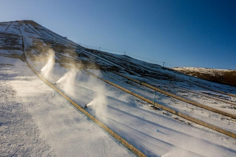 Aerial view of snow cannons spraying artifical snow on a ski slope at El Colorado skiing center in Chile, where climate change and pollution have resulted in diminishing snowfall