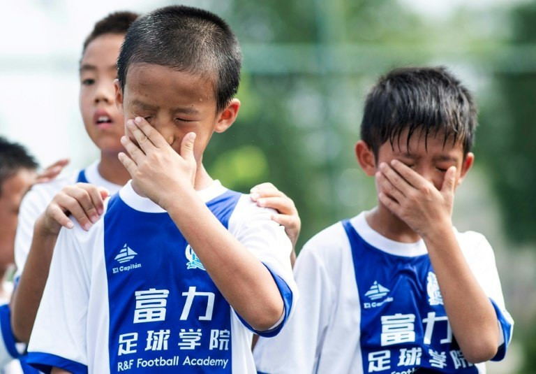 Boys wipe away perspiration during a training session at the Guangzhou R&F Football Academy in Meizhou