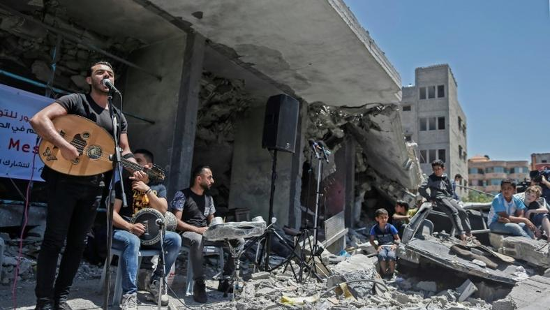 The Palestinian band Dawaween performs on May 14, 2019 on the rubble of a building in the Gaza Strip that was recently destroyed by Israeli air strikes during an event calling for a boycott of the Eurovision song contest hosted by Israel