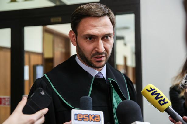 Obrońca Dariusza K. - mec. Marcin Kondracki rozmawia z dziennikarzami na korytarzu sądowym.