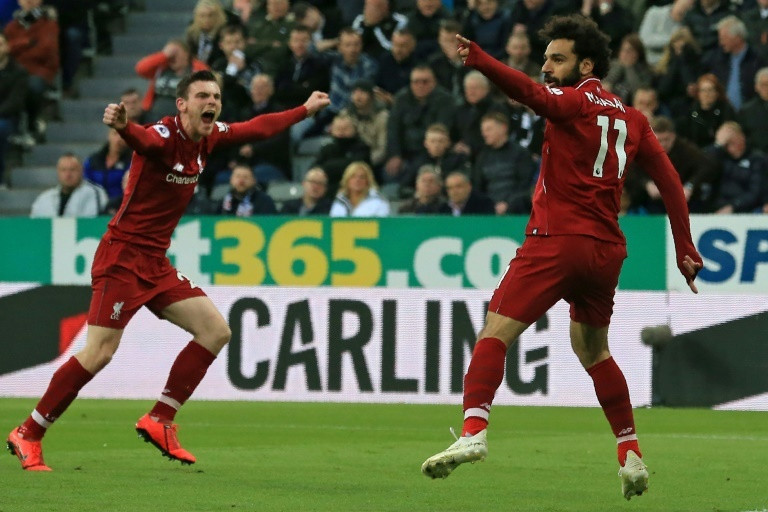 Liverpool's Egyptian midfielder Mohamed Salah (R) celebrates with Liverpool's Scottish defender Andrew Robertson (L) after scoring their second goal during the English Premier League football match between Newcastle United and Liverpool at St James' Park in Newcastle-upon-Tyne, north east England on May 4, 2019 (AFP)