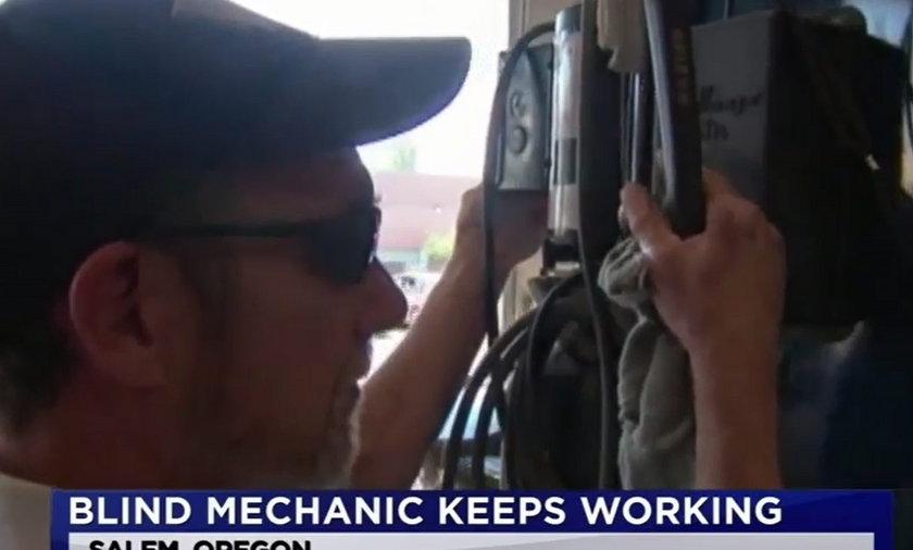 Niewidomy mechanik naprawia samochody w warsztacie.