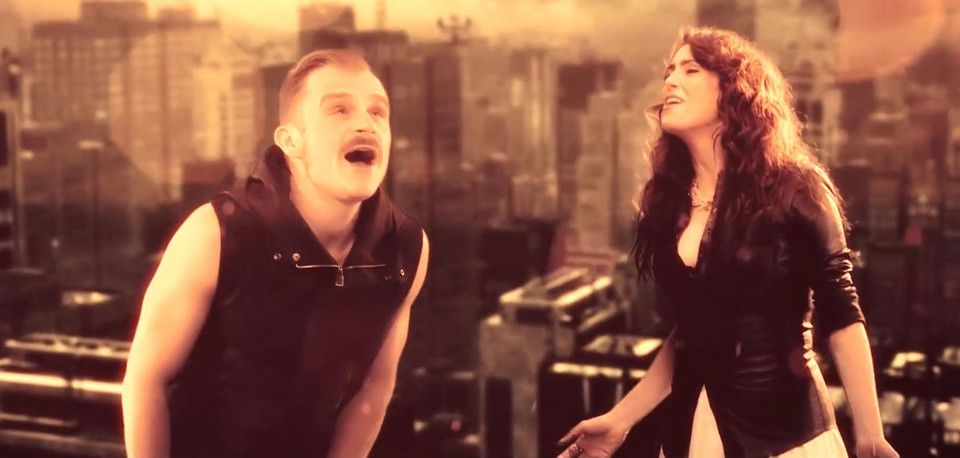 "Piotr Rogucki i Sharon den Adel (screen z klipu ""Whole World is Watching"")"