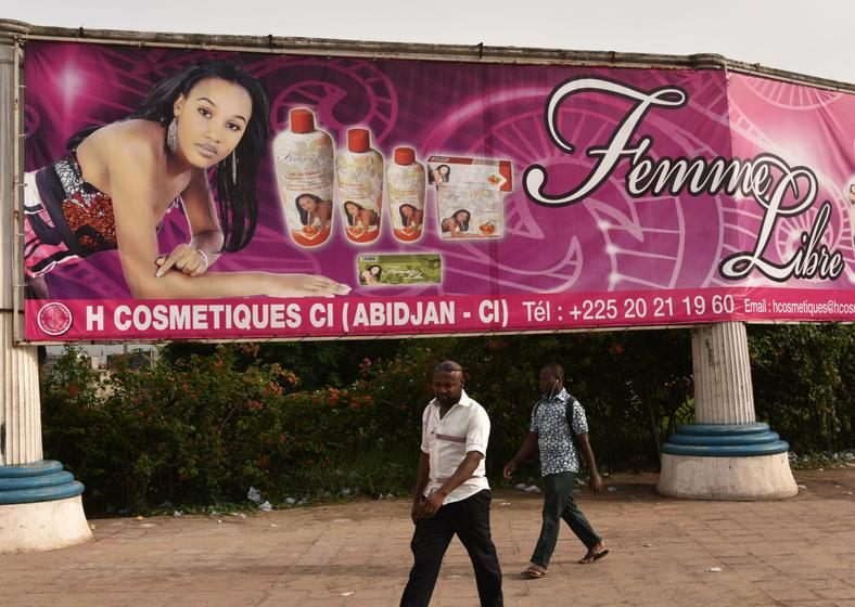 Two men walk under a giant advertising placard of skin-lightening products in Abidjan.