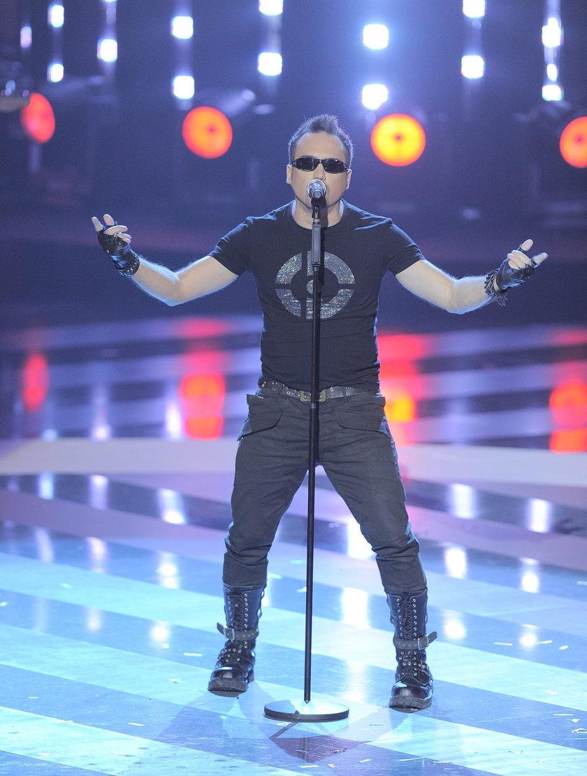 Szymon Wydra na scenie z mikrofonem i w ciemnych okularach