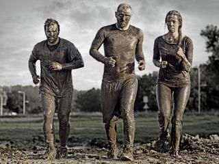group of people jogging in mud