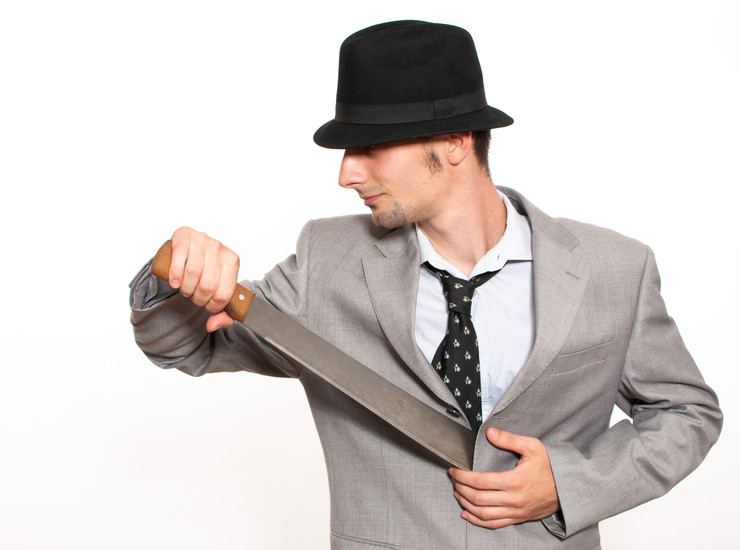 stock-photo-handsome-young-caucasian-businessman-pulling-out-a-machete-from-his-suit-187618640