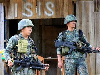 Soldiers stand guard along the main street of Mapandi village as government troops continue their as