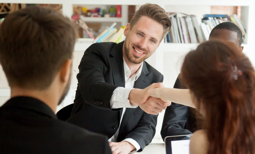Smiling businessman and businesswoman shaking hands sitting at m
